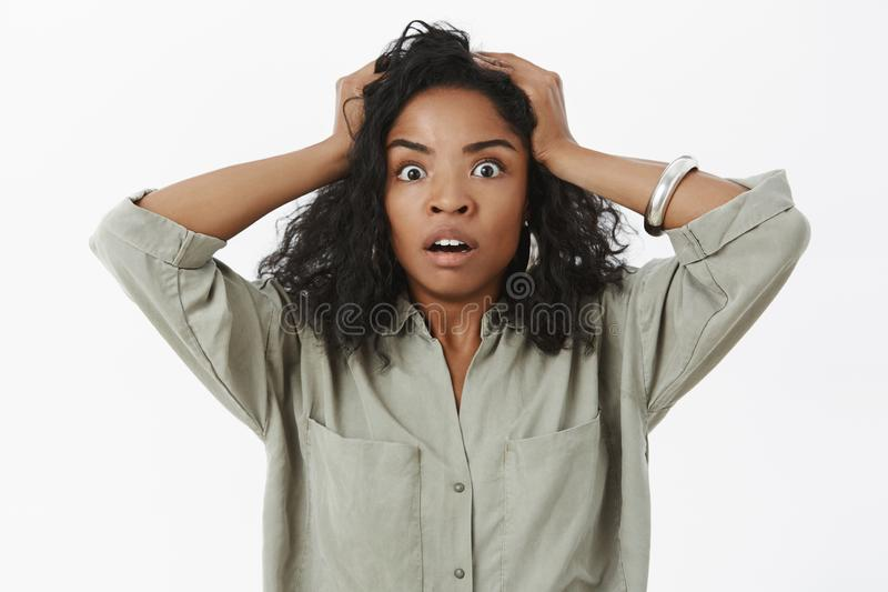Waist-up shot of concerned girl in stupor. Portrait of shocked african american businesswoman standing anxious and royalty free stock images