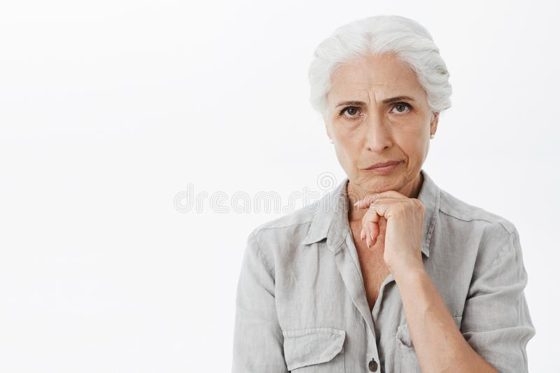 Waist-up shot of concerned serious-looking perplexed elderly woman with grey hair frowning and smirking from. Dissatisfaction holding hand on chin thinking stock photos