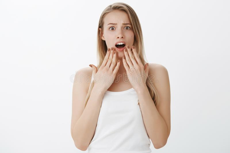 Waist-up shot of concerned and shocked worried young girl with blond hair dropping jaw gasping and covering opened mouth stock photography