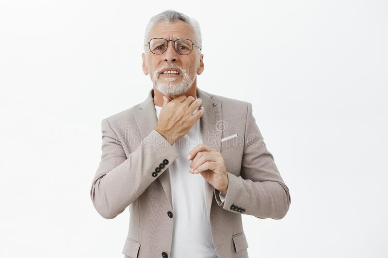 Waist-up shot of concerned and troubled insecure old male entrepreneur in glasses and suit with white hair feeling sick. Touching neck suffering from sore stock photo