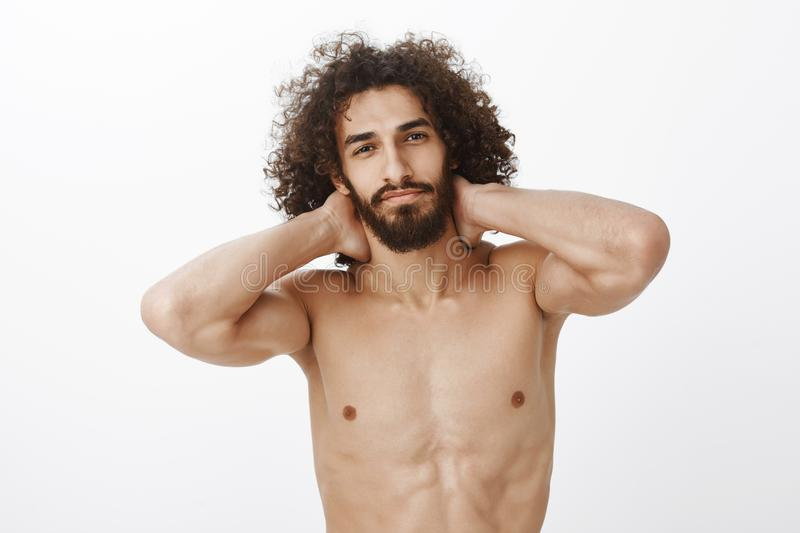 Waist-up shot of confident beautiful hispanic bearded guy with curly hair, holding hands behind neck, standing naked stock photo