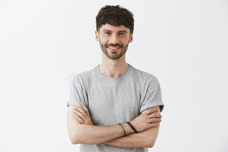 Waist-up shot of confident good-looking mature european male entrepreneur in t-shirt holding hands crossed in self. Assured pose and smiling with assured stock photo