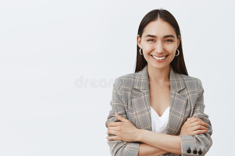 Waist-up shot of confident happy female entrepreneur in stylish jacket over t-shirt, holding hands crossed on chest in. Self-assured pose, smiling broadly at royalty free stock photos