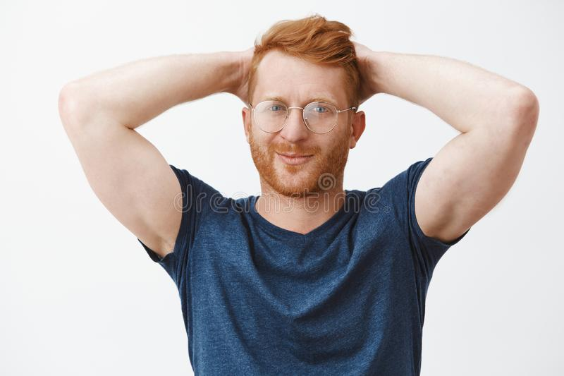Waist-up shot of confident and relaxed masculine redhead caucasian guy in glasses and blue t-shirt, holding hands behind stock photos