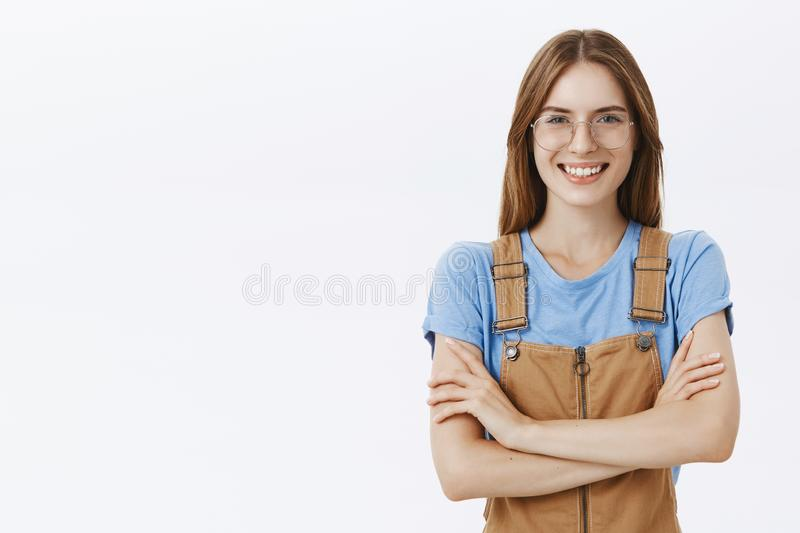 Waist-up shot of confident self-assured charismatic and smart woman in glasses holding hands crossed on chest smiling. Broadly with assertive and determined stock image