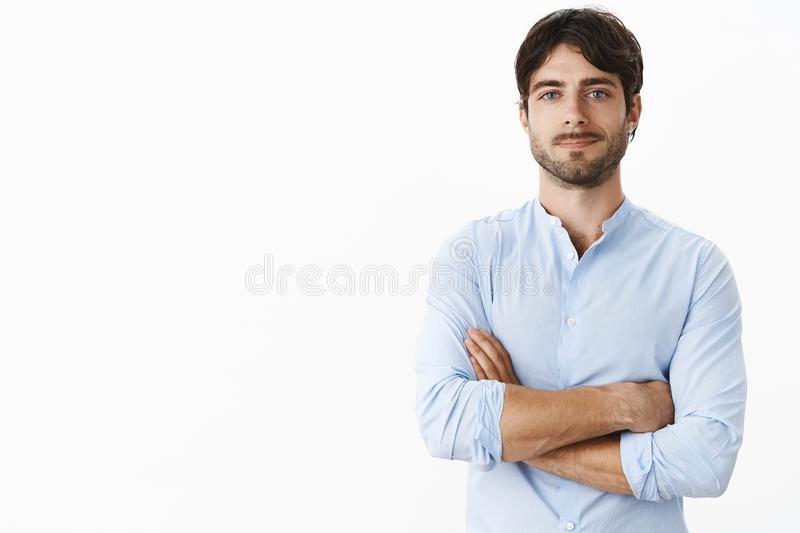 Waist-up shot of confident successful handsome entrepreneur with blue eyes and bristle in blue shirt holding hands. Crossed on chest in self-assured gesture royalty free stock images