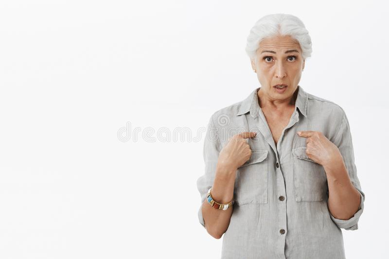 Waist-up shot of confused and stunned senior woman feeling questioned and frustrated pointing at herself staring stock image