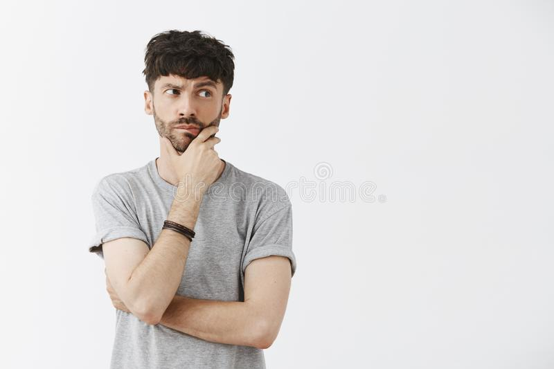 Waist-up shot of creative and artistic caucasian male model with beard holding hand on jaw and chin gazing right with stock photography