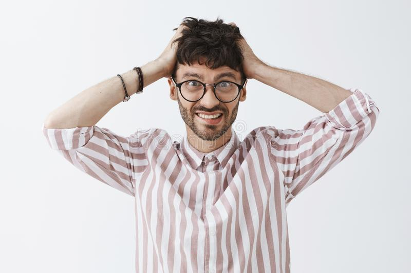 Waist-up shot of creative confused and worried good-looking male artist in glasses and stylish striped shirt holding stock photo