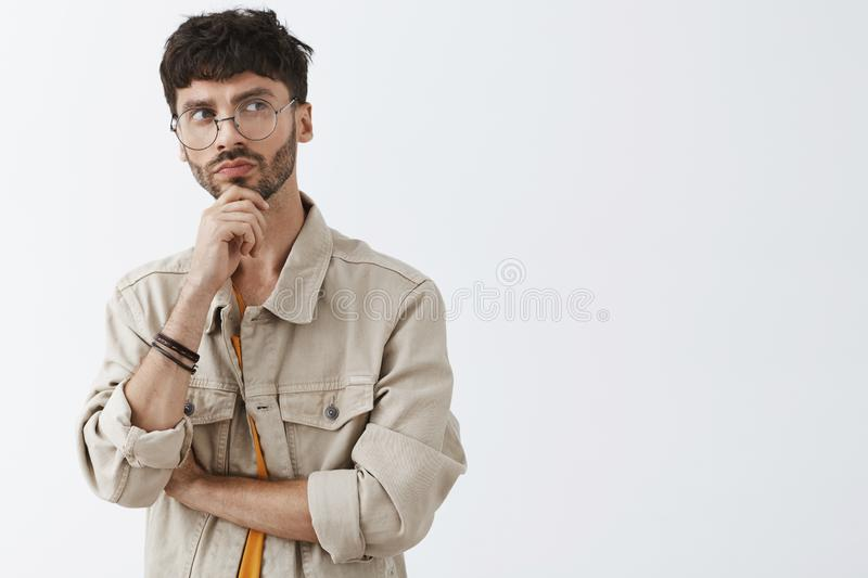 Waist-up shot of creative european dark-haired man with beard in trendy glasses and beige shirt holding hand on chin and stock photo