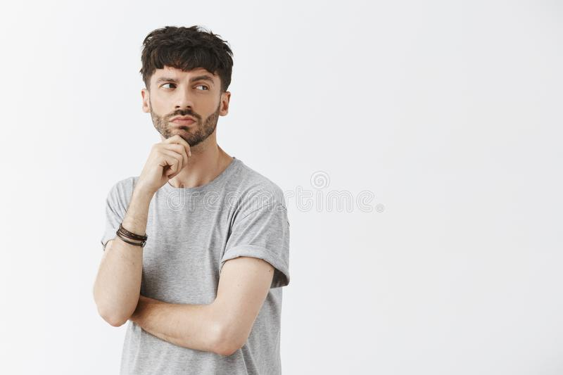 Waist-up shot of creative thoughtful intrigued good-looking guy with beard holding hand on chin turning right and gazing. While thinking being curious and royalty free stock photo