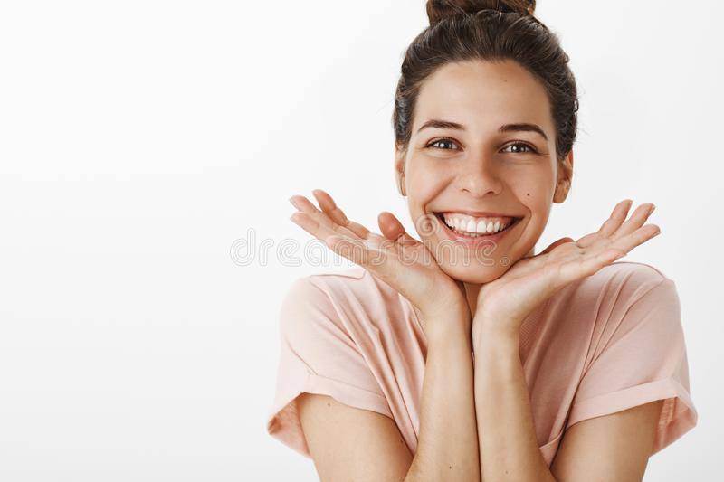 Waist-up shot of cute charismatic and happy girl in love feeling awesome and joyful leaning head on hands showing pure. Clean skin and smiling broadly achieving royalty free stock photo