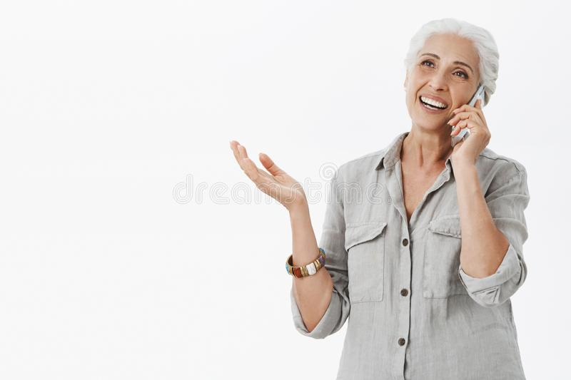 Waist-up shot of delighted caefree kind grandmother talking on telephone and gesturing while being excited and carried. Away with conversation gazing left stock images