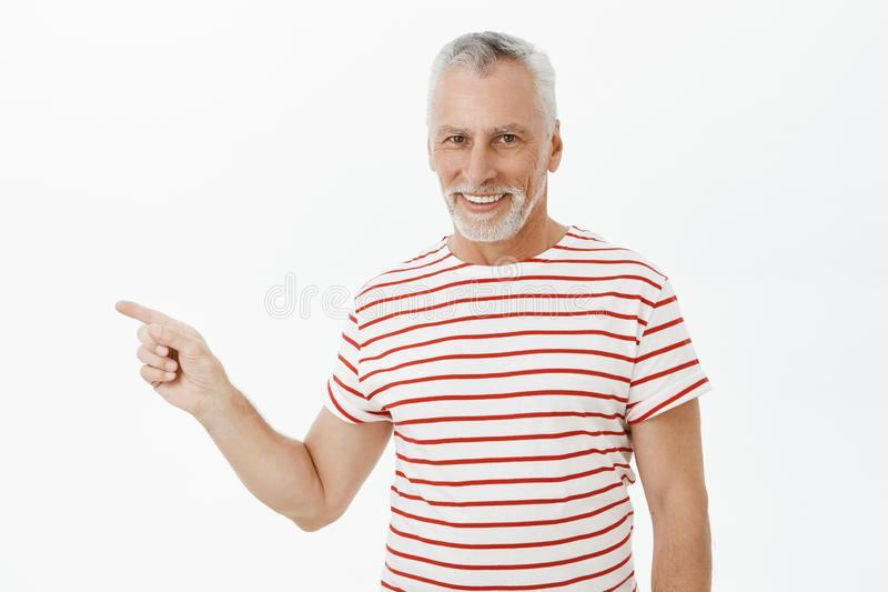 Waist-up shot of delighted carefree charismatic happy old man with grey beard in striped t-shirt smiling satisfied and stock photos