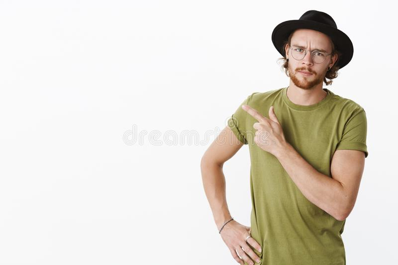 Waist-up shot of disappointed gloomy and displeased redhead guy in glasses and hat with beard pointing at upper left stock photos