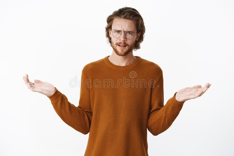 Waist-up shot of displeased and disappointed good-looking young male in glasses and brown sweater frowning with raised stock photo