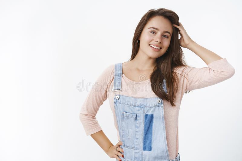 Waist-up shot of dreamy happy young female brunette touching hair delighted smiling with white perfect teeth at camera royalty free stock photo