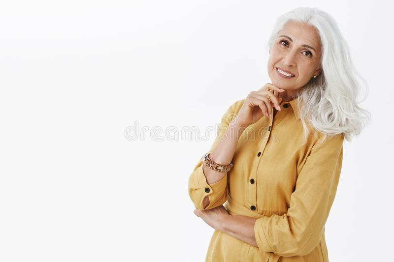 Waist-up shot of elegant stylish and happy elder woman with grey pretty hairsyle holding hand above chin standing half stock photo