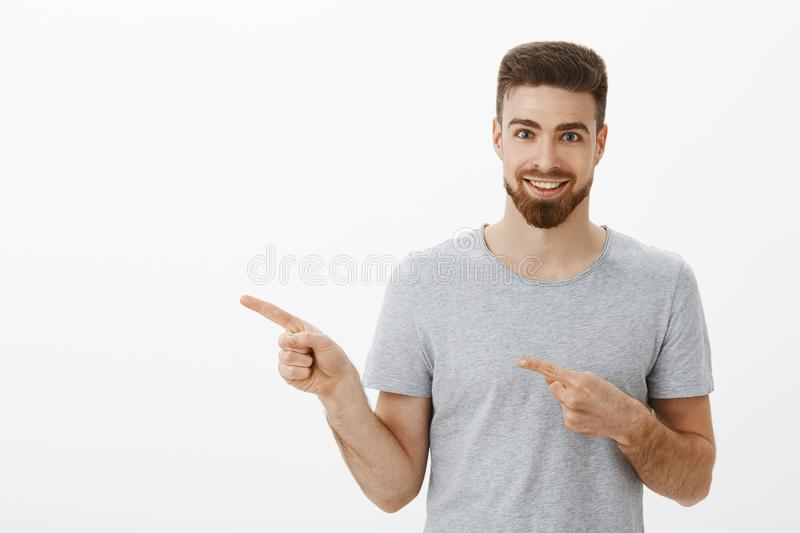 Waist-up shot of enthusiastic and charismatic handsome sportsman with beard and white pleasant smile pointing left with stock photos