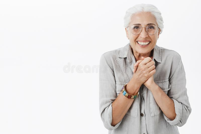 Waist-up shot of excited enthusiastic and happy elderly woman in glasses and shirt clenching palms together over chest royalty free stock photo