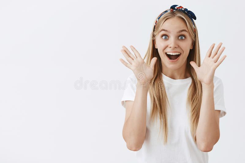 Waist-up shot of excited and thrilled charming blonde female student in headband and casual white shirt raising palms royalty free stock images