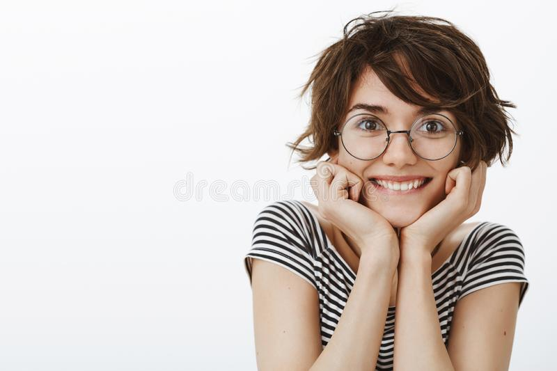 Waist-up shot of feminine cute woman with short brown haircut in glasses, smiling broadly, leaning head on palms, gazing royalty free stock images