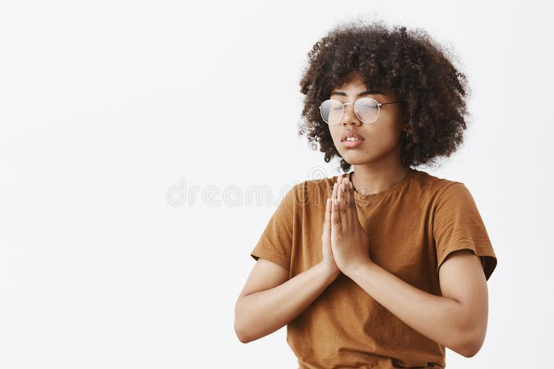 Waist-up shot of focused relaxed and calm attractive young dark-skinned female in glasses with afro hairstyle standing. Half-turned to left with closed eyes stock image