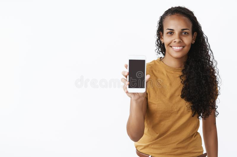 Waist-up shot of friendly creative and stylish attractive dark-skinned female holding smartphone showing cellphone. Screen at camera and smiling delighted as royalty free stock photography