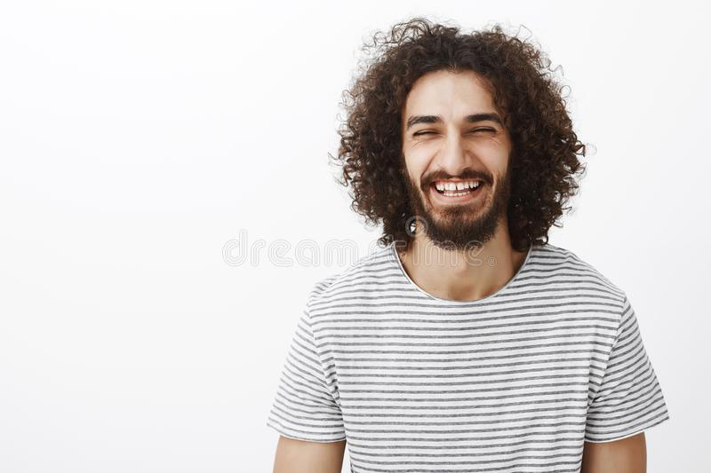 Waist-up shot of friendly happy hispanic bearded guy with curly hair, wearing stylish striped t-shirt, laughing out loud stock photos