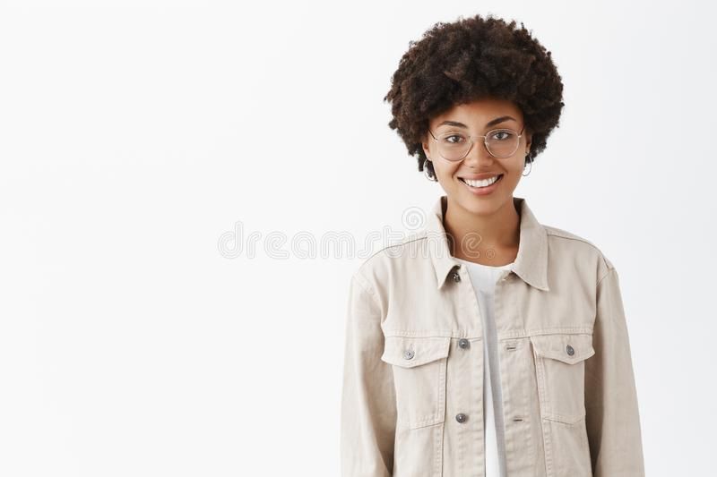 Waist-up shot of friendly-looking casual boyish dark-skinned woman with afro hairstyle in glasses and trendy shirt. Smiling broadly and standing over gray wall royalty free stock photo