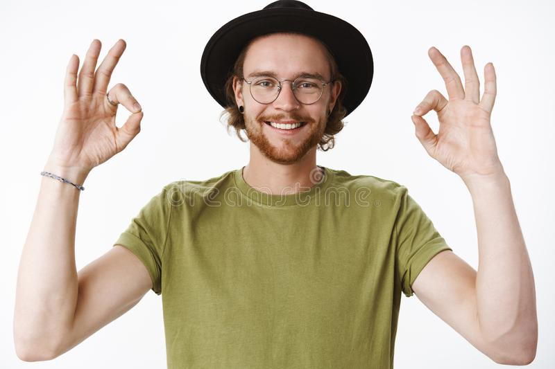 Waist-up shot of friendly-looking energized and pleased young creative bearded male in glasses and hat showing okay stock photography