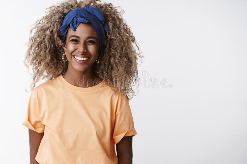 Waist-up shot friendly and sincere, attractive african-american blond girl with afro hairstyle, stylish headband and. Orange t-shirt, laughing and smiling royalty free stock photo