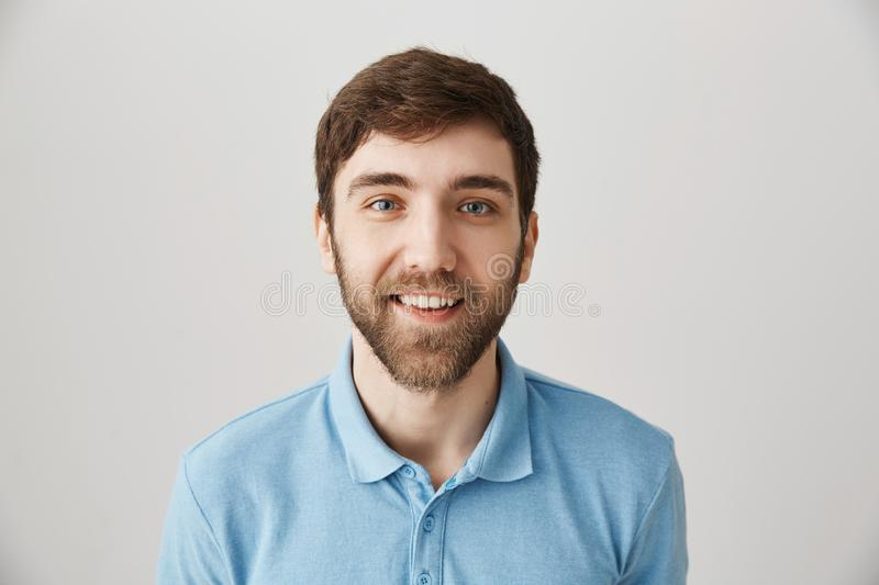 Waist-up shot of funny emotive adult bearded guy in blue polo shirt, making faces, smiling broadly and glancing with royalty free stock photos