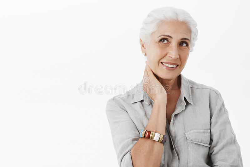 Waist-up shot of gentle delighted european senior female with white hair touching neck and smiling joyfully gazing at royalty free stock photo