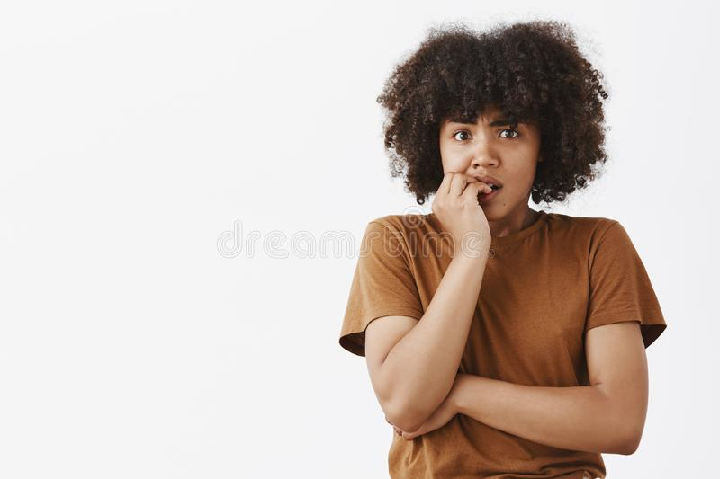 Waist-up shot of girl scared of consequences. Nervous panicking dark-skinned girlfriend with afro hairstyle biting. Fingernails and gazing worried at camera as royalty free stock image
