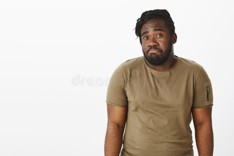 Waist-up shot of gloomy unaware dark-skinned man with beard, shrugging and pulling lips down, being unhappy and confused. Standing clueless over gray royalty free stock photography
