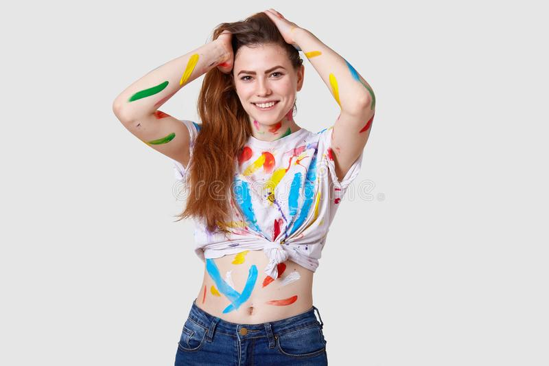 Waist up shot of good looking cheerful woman with dark long hair, positive expression, dressed in casual outfit, being dirty from. Paints, creats picture stock photos