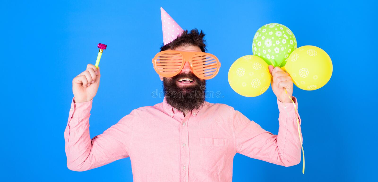 Waist up shot of good looking positive man with beard holding helium balloons and whistle smiling broadly, having fun on. Party. People, joy, entertainment and stock photo