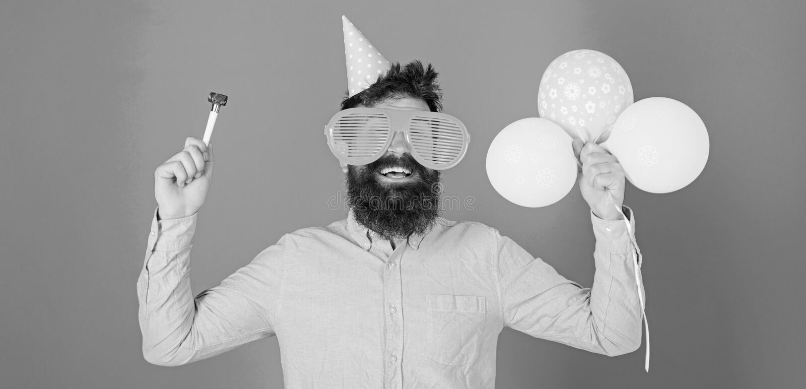 Waist up shot of good looking positive man with beard holding helium balloons and whistle smiling broadly, having fun on. Party. People, joy, entertainment and stock photos