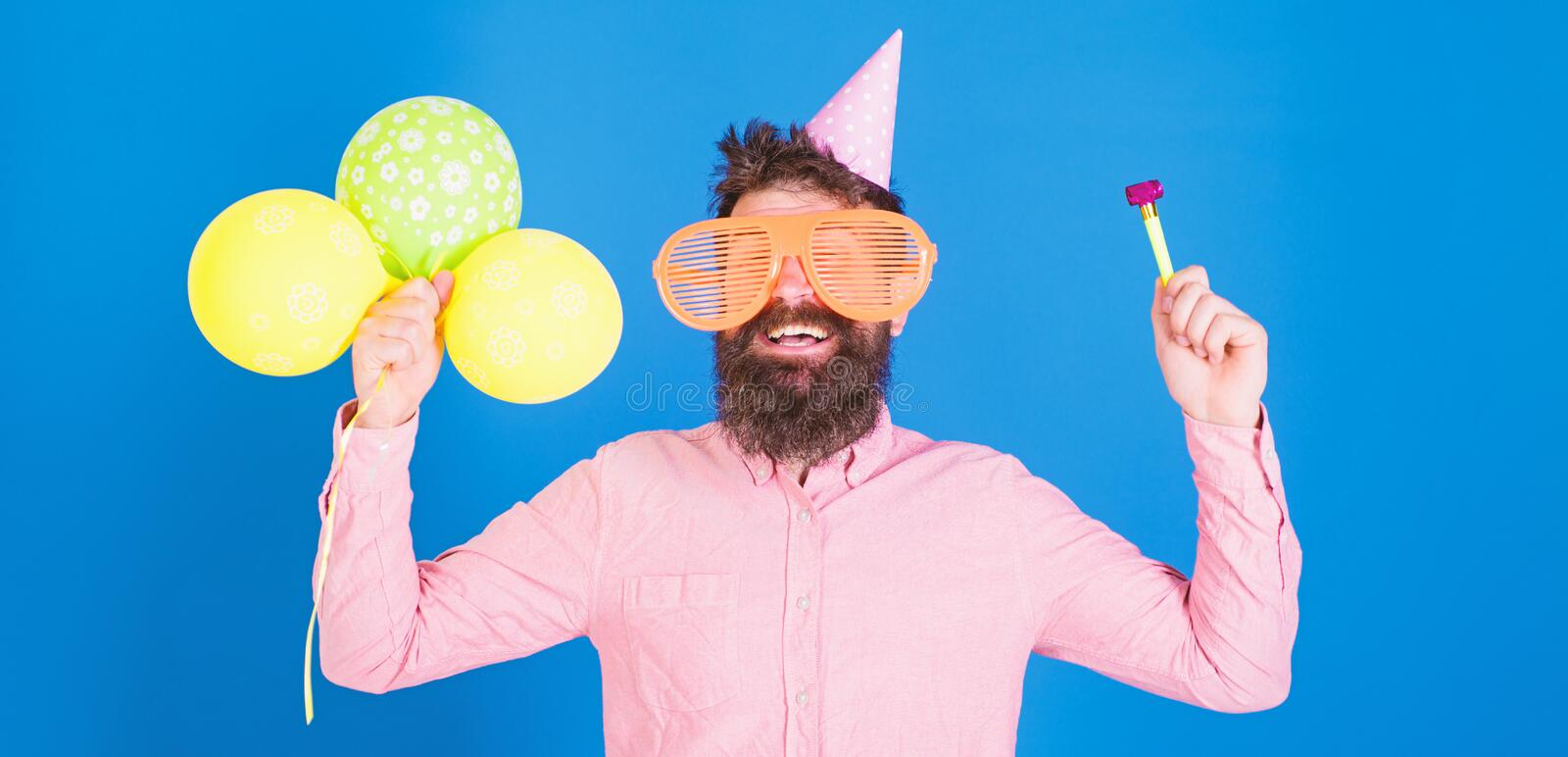 Waist up shot of good looking positive man with beard holding helium balloons and whistle smiling broadly, having fun on. Party. People, joy, entertainment and royalty free stock photos