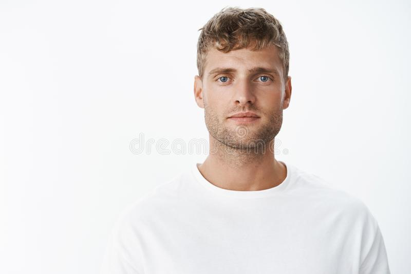 Waist-up shot of handsome calm blond blue-eyed guy with bristle in white t-shirt looking at camera with relaxed carefree stock photos