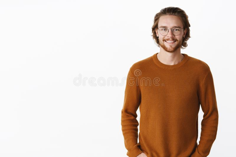 Waist-up shot of handsome charming bearded man in glasses with long wavy hair in sweater smiling joyfully at camera as stock photography