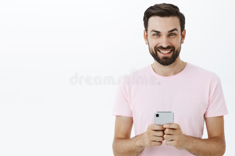 Waist-up shot of handsome delighted and carefree european man with beard and blue eyes holding smartphone looking stock image