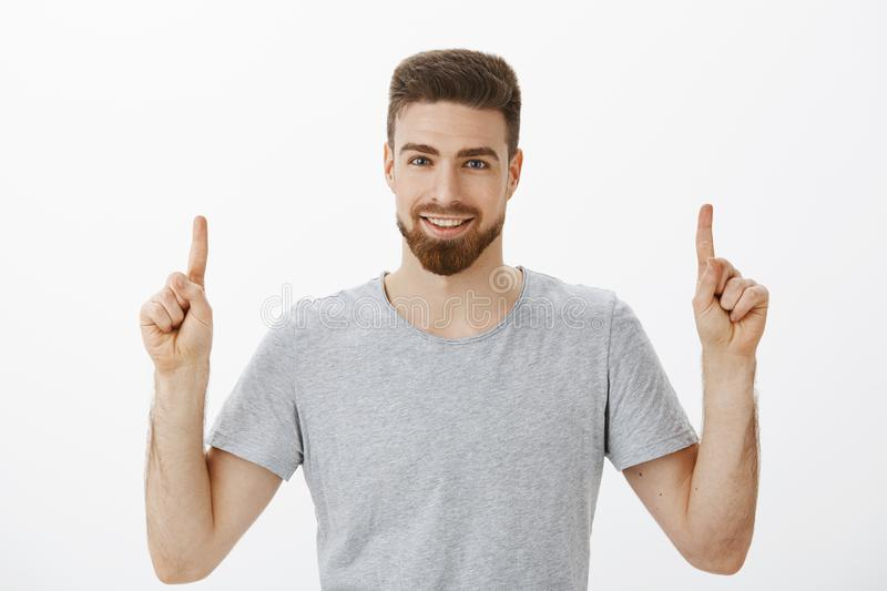 Waist-up shot of handsome self-assured male entrepreneur with beard and brown hairstyle raising index fingers pointing. Up with confident delighted look royalty free stock image