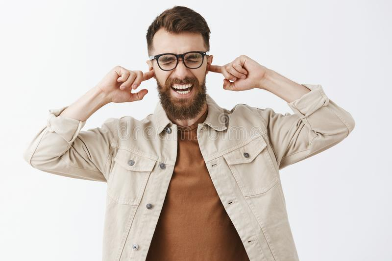 Waist-up shot of handsome stylish hipster guy being in unconmfortable situation covering ears with index fingers. Screaming and closing eyes from discomfort royalty free stock image