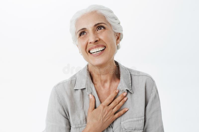 Waist-up shot of happy and delighted grateful charming old lady with white hair holding palm on chest in thankful royalty free stock photo