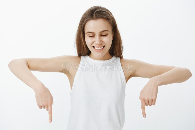 Waist-up shot of happy emotive young woman in casual outfit, looking and pointing down with index fingers, smiling. Broadly and laughing from positive emotions stock images