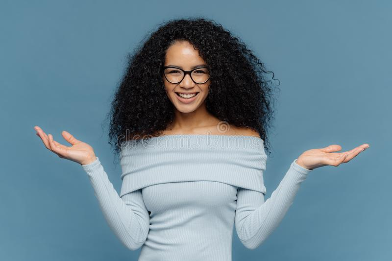 Waist up shot of happy young crisp Afro American woman raises both hands, pretends holding something, wears blue sweater, has. Naked shoulders, optical glasses stock photography