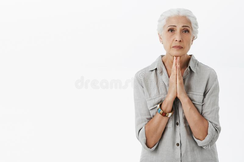 Waist-up shot of hopeful calm and serious-looking old woman holding hands in pray looking at camera with hope and faith stock image