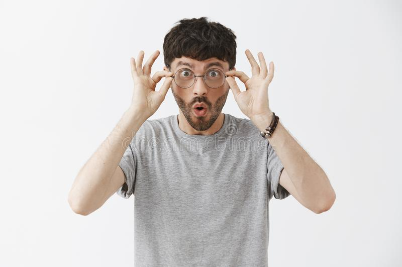 Waist-up shot of impressed and amazed handsome young male programmer in grey t-shirt touching glasses and saying wow stock photo